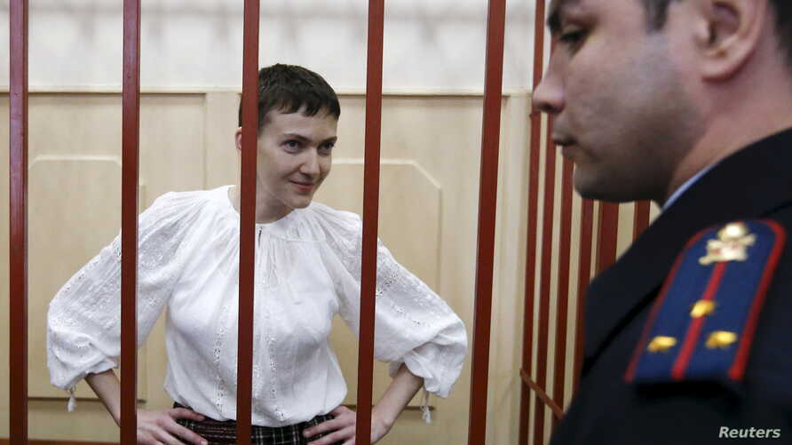 Ukrainian military pilot Nadezhda Savchenko stands inside a defendants' cage as she attends a court hearing in Moscow, April 17, 2015.