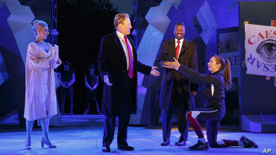 In this May 21, 2017 photo provided by The Public Theater, Tina Benko, left, portrays Melania Trump in the role of Caesar's wife, Calpurnia, and Gregg Henry, center left, portrays President Donald Trump in the role of Julius Caesar during a dress reh