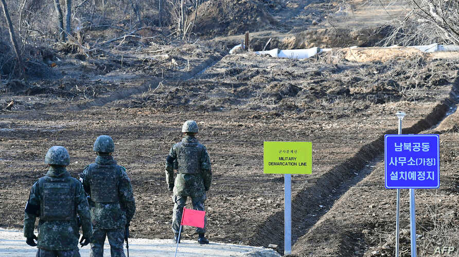 South Korean soldiers stand at Arrowhead Ridge, a site of battles in the 1950-53 Korean War, as a tactical road is built across the military demarcation line inside the Demilitarized Zone (DMZ) in the central section of the inter-Korean border in Che...