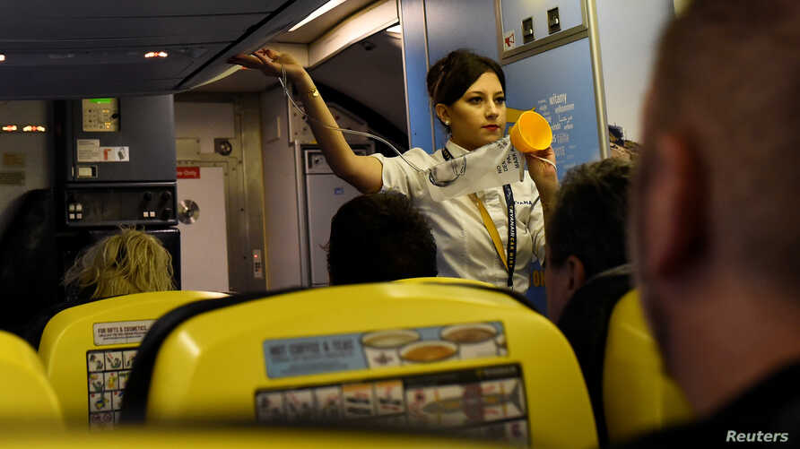 FILE - A Ryanair air steward demonstrates safety procedures before take-off at Dublin airport in Dublin, Ireland, Sept. 27, 2017.