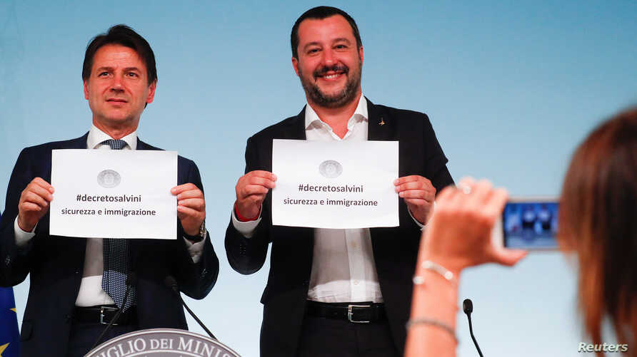 Italy's Prime Minister Giuseppe Conte and Interior Minister Matteo Salvini hold up pieces of paper with the name of the new decree written on them as they are pictured during a news conference at Chigi Palace in Rome, Italy, Sept. 24, 2018.
