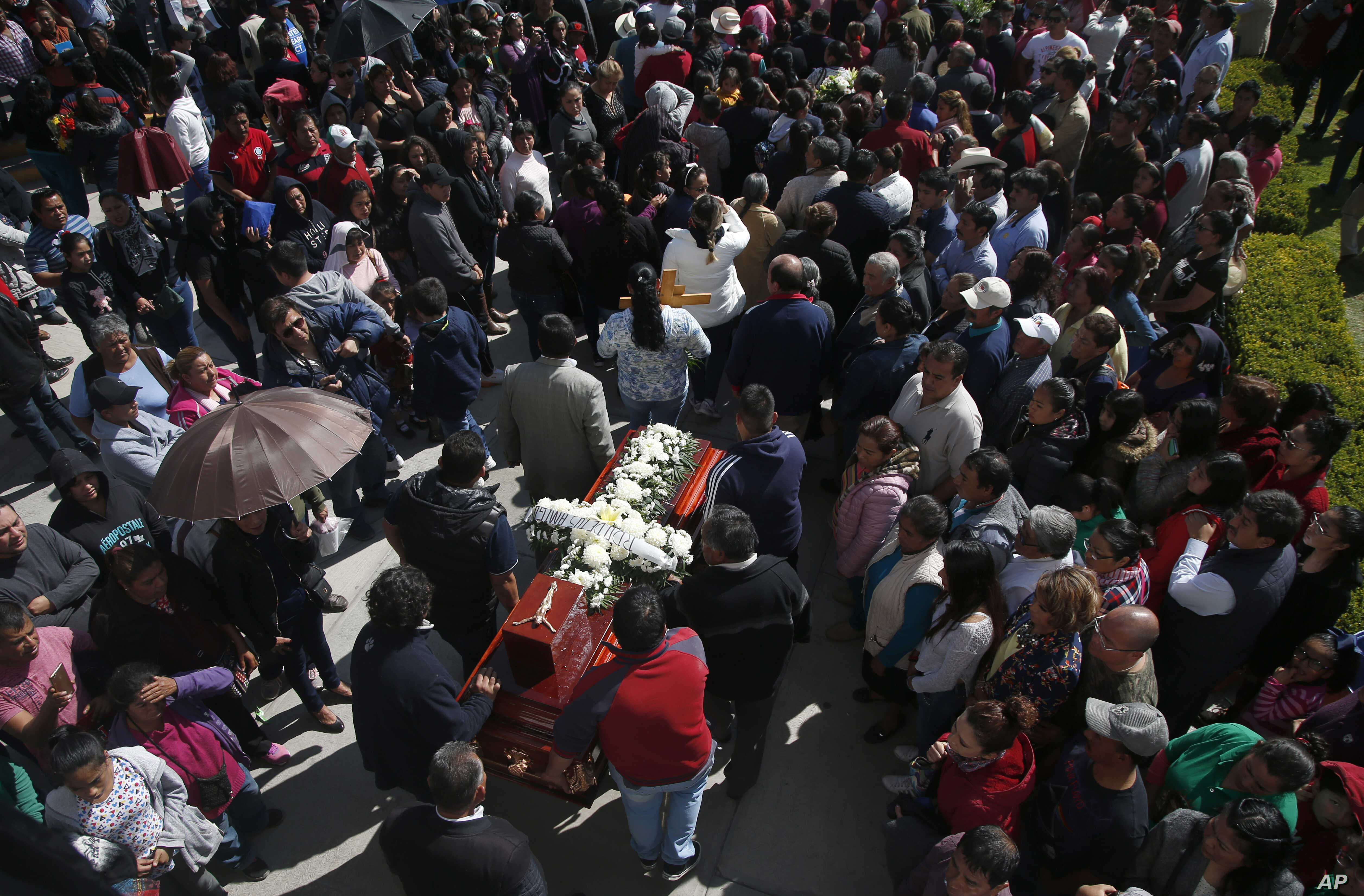 People hold a funeral for a person who died when a gas pipeline exploded in the village of Tlahuelilpan, Mexico, Jan. 20, 2019.
