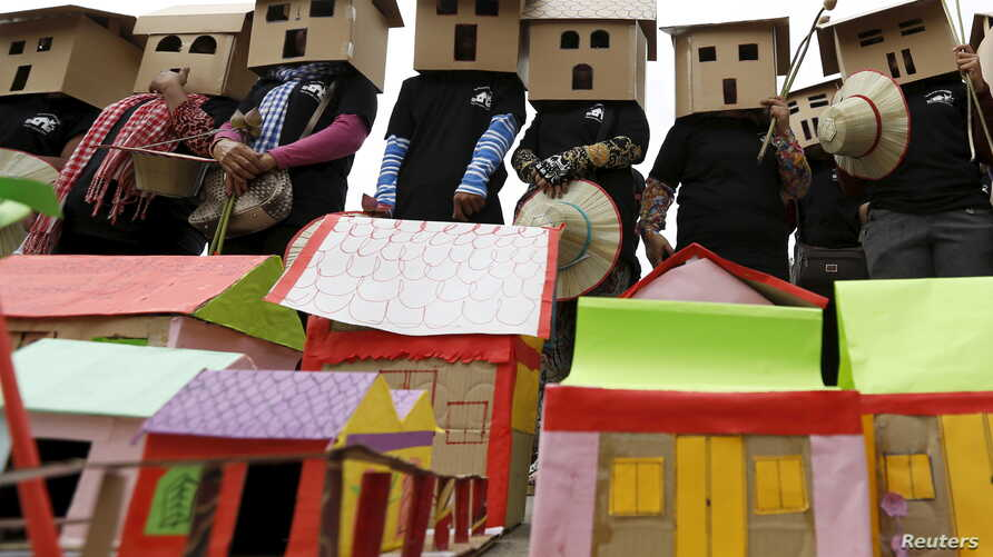 FILE - People wear house models during a march on World Habitat Day in Phnom Penh, Oct. 5, 2015. Former residents of Boeung Kak Lake, Borei Keila neighbourhood and other communities affected by private corporation developers called on the Cambodian g