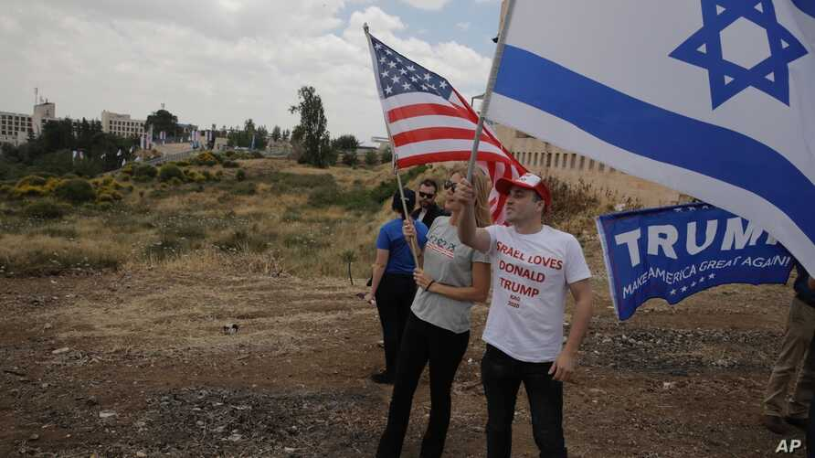 FILE - Israelis hold American and Israeli flags with the new U.S. Embassy in the background in Jerusalem, May 14, 2018. Seventy years after Israel's founding, images of victory and violence showcased the contradictions that bedevil the Jewish state.