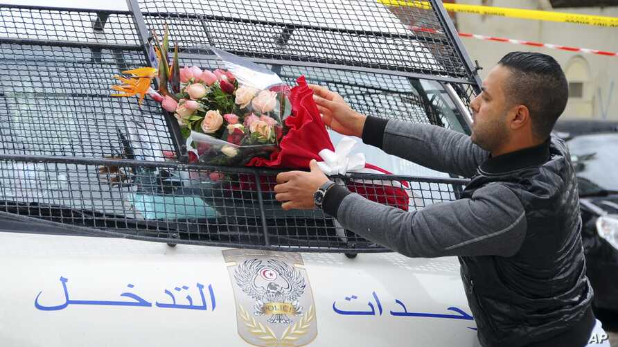 A man places a bouquet of flowers on a police van, near the bus that exploded Tuesday in Tunis, Nov.25, 2015.