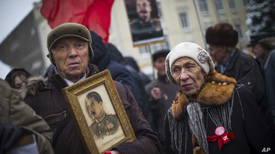 FILE - A man holds a portrait of Soviet dictator Josef Stalin during a demonstration marking the 99th anniversary of the 1917 Bolshevik Revolution in Moscow, Russia, Nov. 7, 2016. Unlike the past, Nov. 7 is no longer a public holiday in Russia.