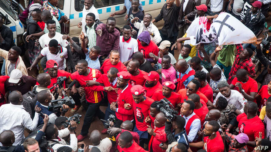 Musician turned politician Robert Kyagulanyi (C) is joined by other activists in Kampala, Uganda, July 11, 2018 in Kampala during a demonstration to protest a controversial tax on the use of social media.