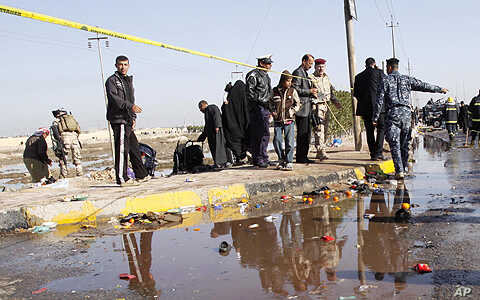 Security forces and people inspect the scene of a bomb attack on Shi'ite pilgrims, near the southern port city of Basra, Iraq's second-largest city, 550 kilometers southeast of Baghdad, Saturday, Jan. 14, 2012.
