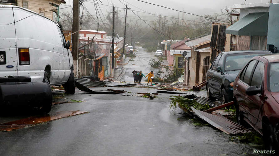 People walk on the street next to debris after the area was hit by Hurricane Maria in Guayama, Puerto Rico, Sept. 20, 2017.