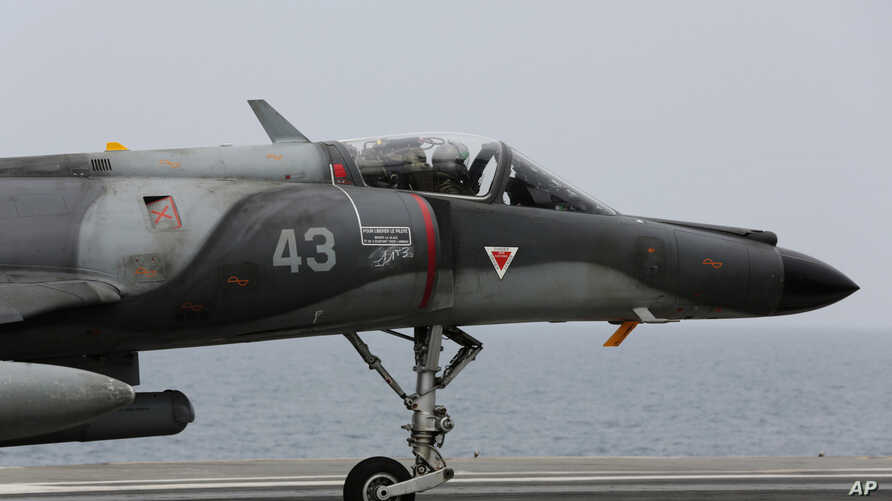 FILE - A French military plane lands on the French navy aircraft carrier Charles de Gaulle in the Persian Gulf, March 18, 2015
