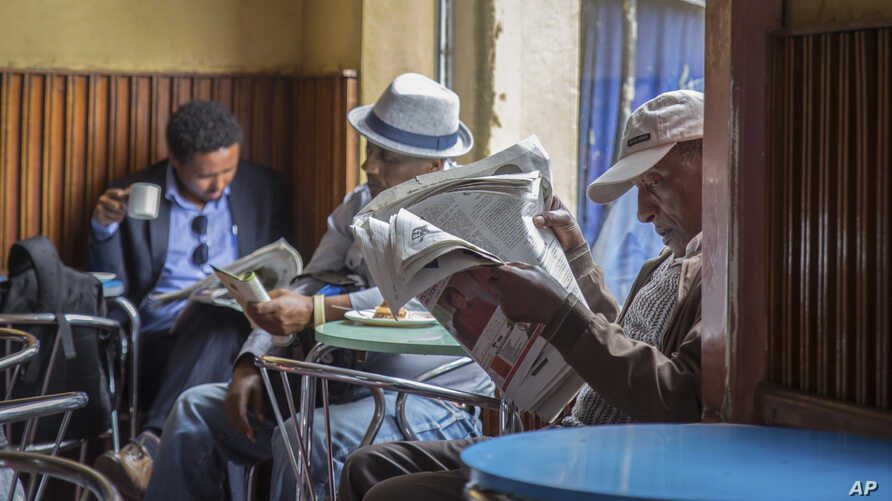 FILE - Ethiopian men read newspapers and drink coffee at a cafe during a declared state of emergency in Addis Ababa, Ethiopia.