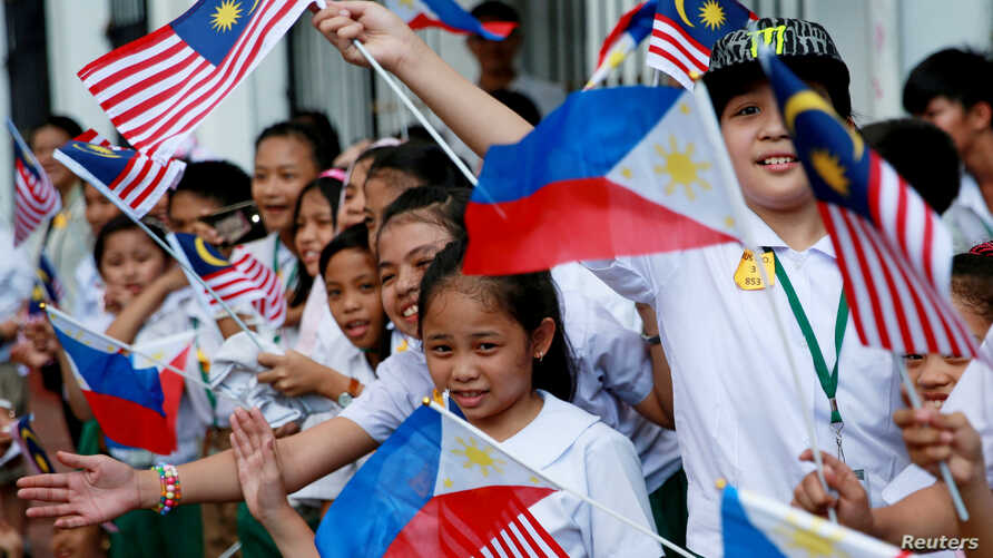 Children wave Philippine and Malaysian flags as they wait for the arrival of Malaysian Prime Mahathir Bin Mohamad at the Malacanang presidential palace in Manila, Philippines, March 7, 2019.