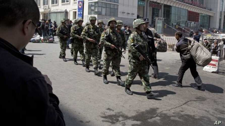 Heavily armed Chinese paramilitary police men march past the site of the April 31 explosion outside the Urumqi South Railway Station in Urumqi in northwest China's Xinjiang Uygur Autonomous Region.  Recent deadly attacks in China blamed on Islamic ex