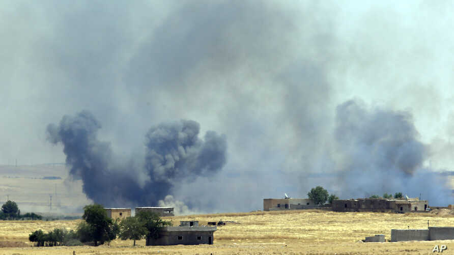 In this photo taken in Akcakale, Sanliurfa province, southeastern Turkey from the Turkish side of the border between Turkey and Syria, smoke from a US-led airstrike rises over the outskirts of Tal Abyad, Syria, June 14, 2015.