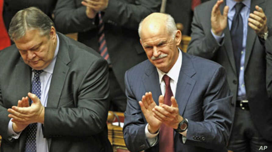 Greek Prime Minister George Papandreou (R) and Finance Minister Evangelos Venizelos applaud after winning a vote of confidence in the Greek parliament in Athens, Greece, November 5, 2011.