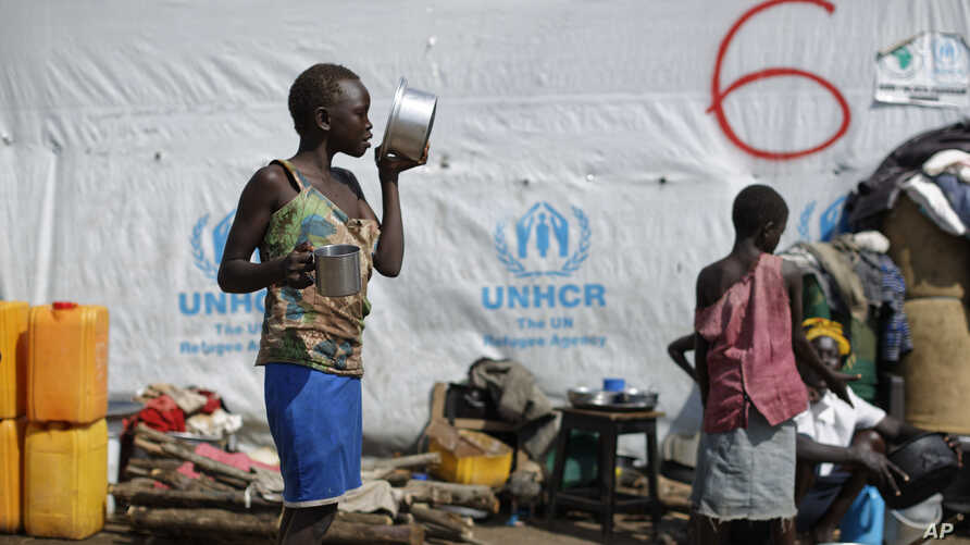 FILE - A South Sudanese refugee girl eats porridge, at the Imvepi intake center, where newly-arrived refugees are processed before being transferred to the nearby Bidi Bidi refugee settlement, in northern Uganda, June 9, 2017.
