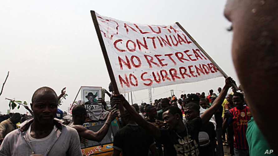 A protester holds a banner on the fourth day of a nationwide strike against the removal of the petrol subsidy in Lagos, January 12, 2012.