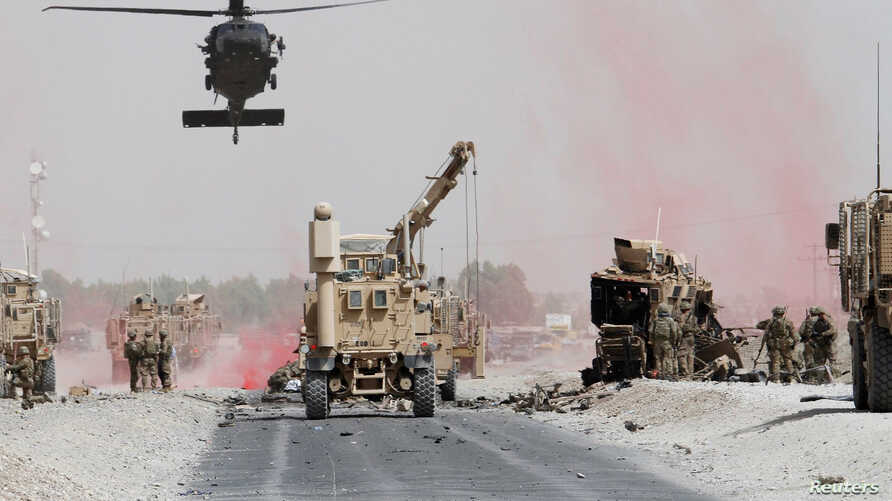 U.S. troops assess the damage to an armored vehicle of a NATO-led military coalition after a suicide bomber's attack in Kandahar province, Afghanistan, Aug. 2, 2017.