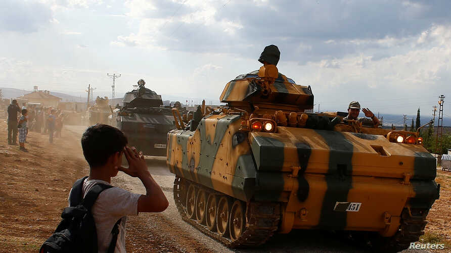 FILE - A boy salutes as Turkish Armed Forces vehicles drive pass by a village on the Turkish-Syrian border line in Reyhanli, Hatay province, Turkey, Oct. 11, 2017.