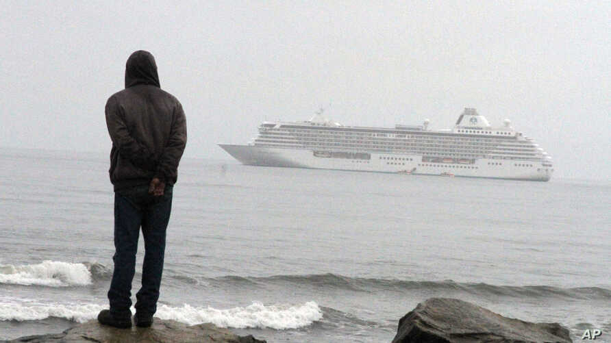 FILE - A man stands on the Bering Sea shore looking at the luxury cruise ship Crystal Serenity anchored just outside Nome, Alaska, Aug. 21, 2016.