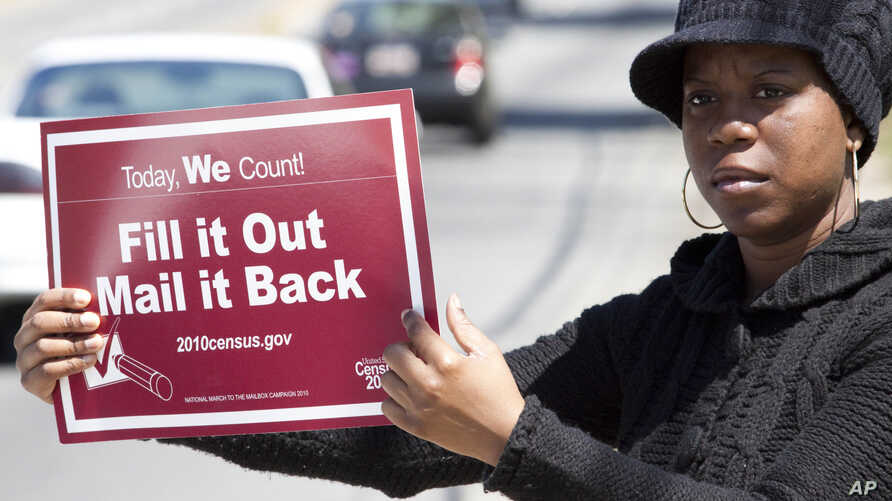 FILE - Shanda Burrell of Charlotte, N.C., holds a sign during a rally by U.S. census advocates at the Mas Jid Ash-Shaheed mosque in Charlotte, aimed at persuading people to fill out the 2010 census form.