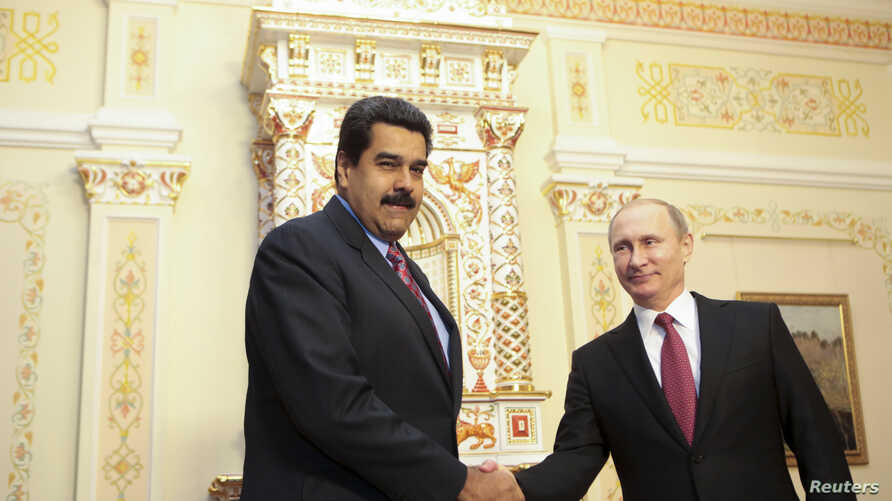 Russian President Vladimir Putin (R) welcomes Venezuela's President Nicolas Maduro in Moscow in this January 15, 2015 handout from the Miraflores Palace. REUTERS/Miraflores Palace/Handout via Reuters (RUSSIA- Tags: POLITICS) ATTENTION EDITORS - THIS