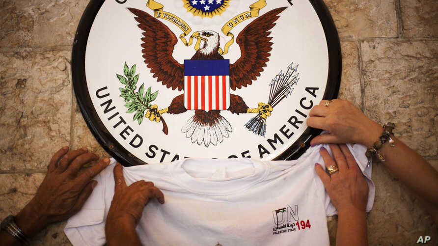 FILE - Palestinian activist place a t-shirt with a logo representing their statehood bid at the UN underneath the US Consulate sign during a small pro-state rally, Wednesday, Sept. 21, 2011 in  Jerusalem, Israel.