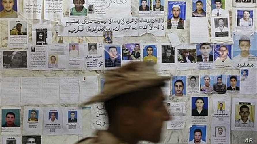 A soldier walks past a wall of posters appealing for information about missing people, at a hospital in Benghazi, Libya, April 17, 2011