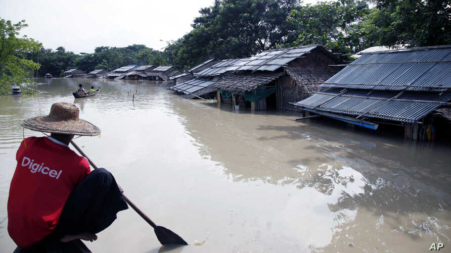 A man paddles his boat near flooded homes in Nyaung Tone, Irrawaddy delta, about 100 kilometers southwest of Yangon, Myanmar, Aug 5, 2015.