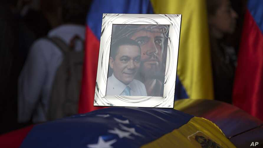 A framed portrait of opposition activist Fernando Alban shadowed by an image of Jesus Christ sits on the flag-draped casket containing his remains, during a solemn ceremony at the National Assembly headquarters, in Caracas, Venezuela, Oct. 9, 2018.