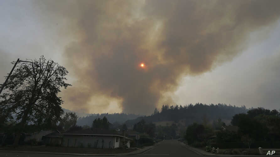 A plume of smoke rises from a mountain over homes in the Oakmont area of Santa Rosa, Calif., Oct. 10, 2017.