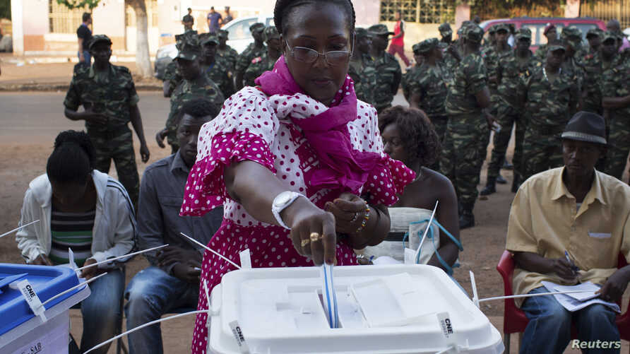 A woman casts her ballot at a polling station as soldiers watch in Bissau, April 13, 2014.
