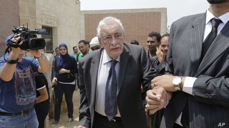 FILE - Egyptian actor Gamil Ratib is helped by a relative as he attends Omar Sharif's burial at the El Shafie Cemetery in Cairo, Egypt, Sunday, July 12, 2015.