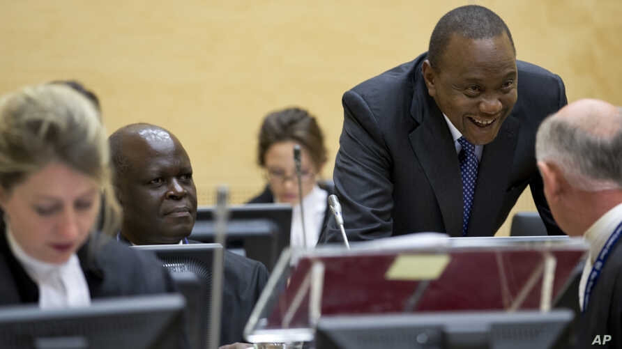 Kenya President Uhuru Kenyatta, second right, talks to his defense team when appearing before the International Criminal Court in The Hague, Netherlands, Oct. 8, 2014.