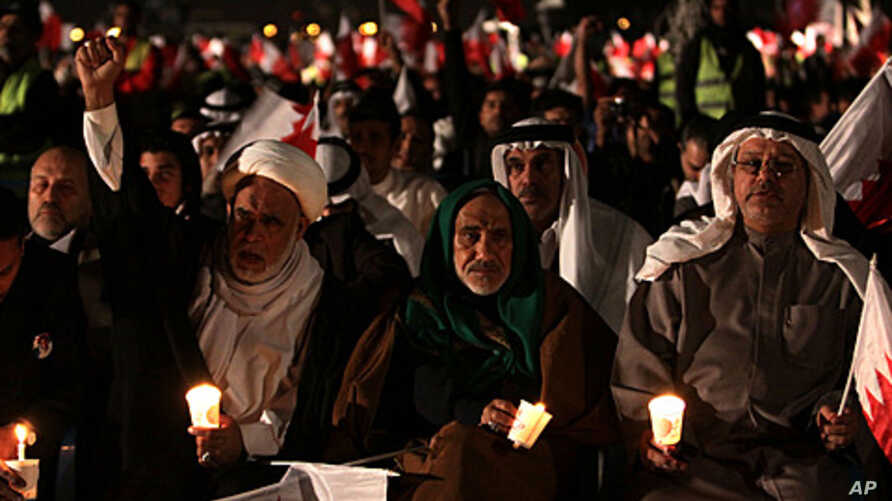 Bahraini  opposition leaders Hamza al-Dairi, second left raising his fist, and Jalal Fairooz, right, holding a candle and Bahraini flag, both former opposition lawmakers from al-Wefaq society, participate in a rally in the eastern village of Sitra, J