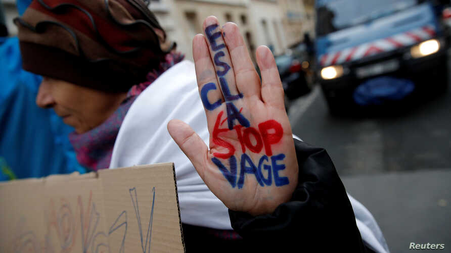 """A woman displays her hand with the message """"Stop Slavery"""" as she attends a protest against slavery in Libya outside the Lybian Embassy in Paris, Nov. 24, 2017."""