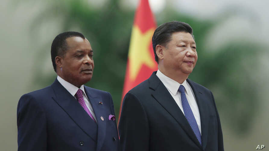 Chinese President Xi Jinping, right, and Congo President Denis Sassou Nguesso listen to their national anthems during a welcoming ceremony inside the Great Hall of the People in Beijing, Sept. 5, 2018.