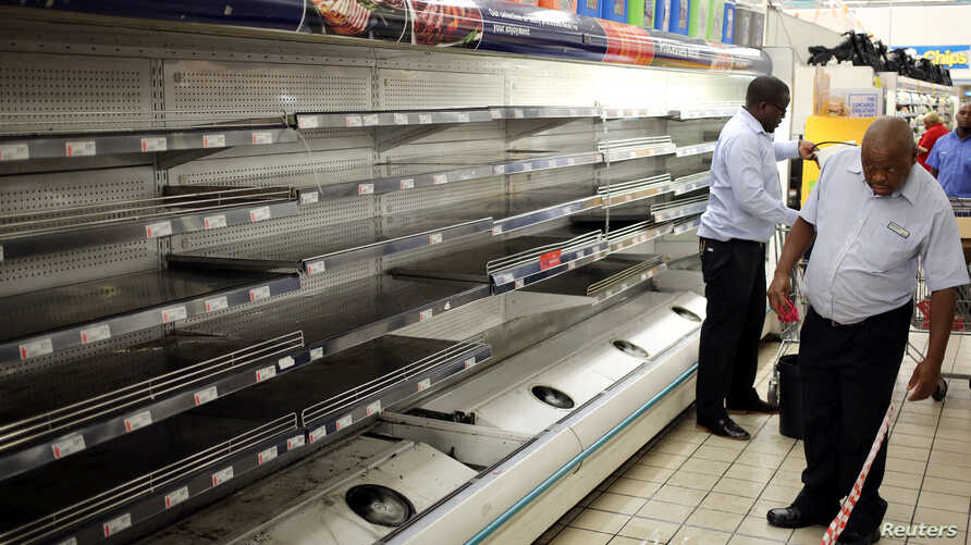 A worker looks at empty shelves after removing processed meat products at a Pick n Pay Store in Johannesburg, South Africa, March 5, 2018, amid the country's worst listeria outbreak on record.
