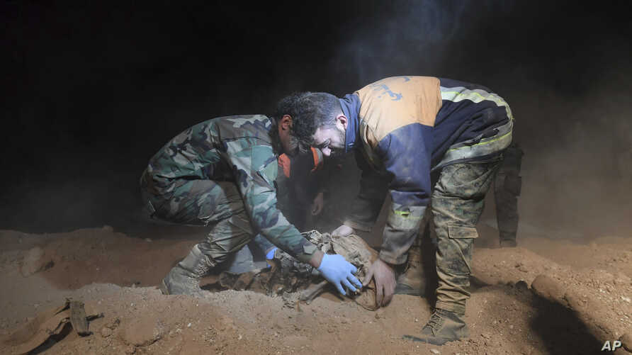 FILE - In this photo released by the Syrian official news agency SANA, Syrian security forces remove human remains at the site of two mass graves believed to contain the bodies of civilians and troops killed by Islamic State militants, in the village
