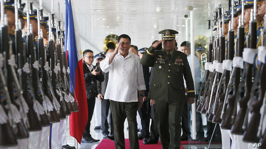 Philippine President Rodrigo Duterte, center left, salutes the troops with Armed Forces Chief Gen. Ricardo Visaya before boarding his flight for a three-day official visit to Japan at the Ninoy Aquino International Airport in suburban Pasay city, sou...