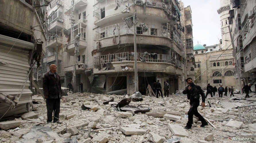 Men inspect the damage at a site hit by what activists said were two barrel bombs dropped by forces loyal to Syria's President Bashar al-Assad in Aleppo's al-Shaar neighborhood February 26, 2015. REUTERS/Rami Zayat (SYRIA - Tags: POLITICS CIVIL UNRES
