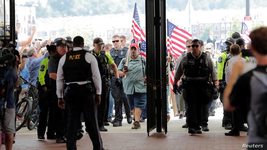 "Police officers await the arrival of Jason Kessler at Vienna Metro Station, on the one year anniversary of the 2017 Charlottesville ""Unite the Right"" protests, in Vienna, Virginia, U.S., August 12, 2018.     REUTERS/Lucas Jackson"