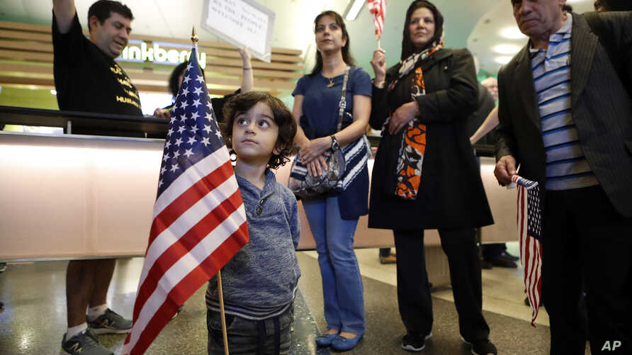 Shayan Ara, 3, holds an American flag as protests against President Donald Trump's executive order banning travel from seven Muslim-majority countries continue at Los Angeles International Airport Sunday, Jan. 29, 2017.