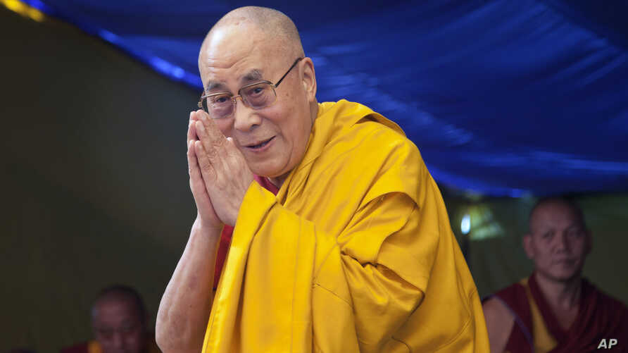 Tibetan spiritual leader the Dalai Lama greets devotees as he arrives to give a religious talk at the Tibetan Children's Village School in Dharmsala, India, May 27, 2015.