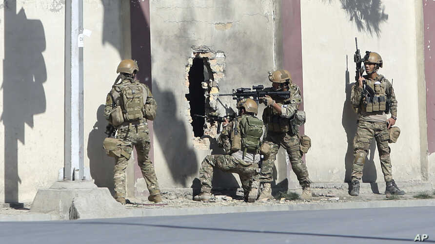 FILE - Afghan security personnel take positions near the Shamshad Television station after a deadly attack in Kabul, Afghanistan, Nov. 7, 2017, for which the Islamic State group claimed responsibility.