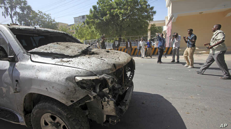 Somali media film near a destroyed vehicle outside the scene of a twin bombing on a hotel in Mogadishu, Feb. 20, 2015.
