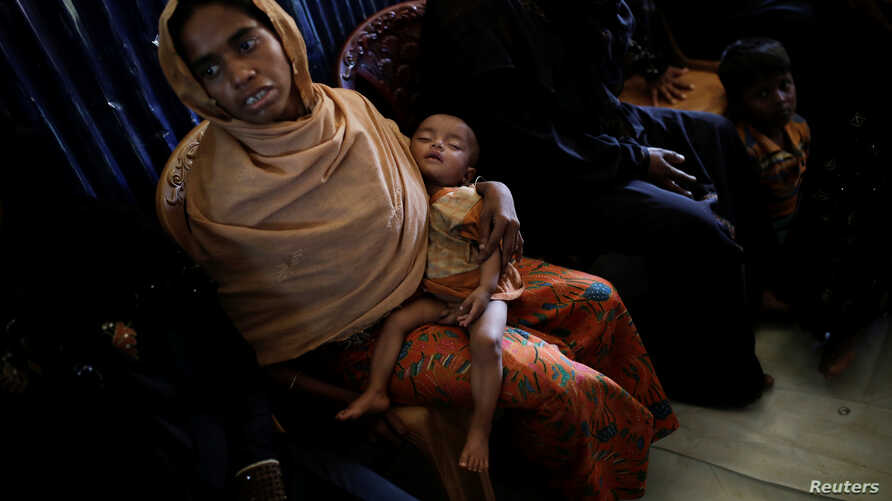 A Rohingya refugee waits for her baby to be examined by doctors at the UNICEF health center at the Kutupalong refugee camp near Cox's Bazar, Bangladesh, Dec. 12, 2017.