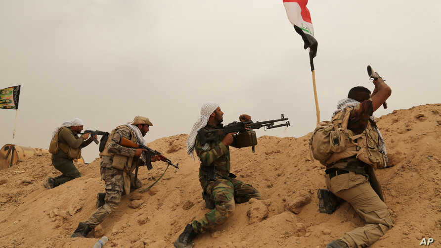 Fighters from Badr Brigades Shiite militia clash with Islamic State group militants at the front line on the outskirts of Fallujah, Anbar province, Iraq, June 1, 2015.