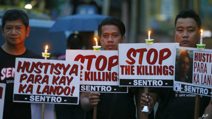"Protesters hold placards in a candlelit protest against extrajudicial killings in President Rodrigo Duterte's ""War on Drugs"" campaign in suburban Quezon city, northeast of Manila, Philippines, Oct. 8, 2016."