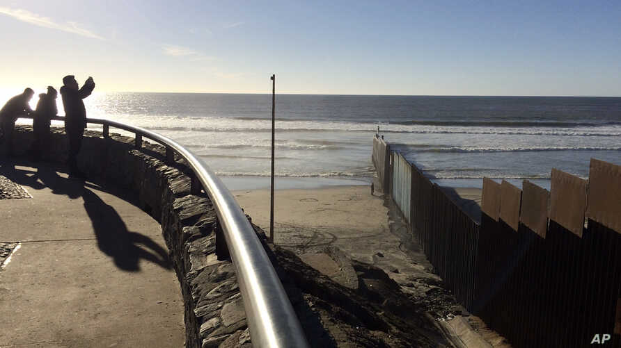 People look out toward where border structure separates San Diego, right, from Tijuana, Mexico, left, Jan. 25, 2017. President Donald Trump moved aggressively to tighten the nation's immigration controls Wednesday, signing executive actions to jump-s